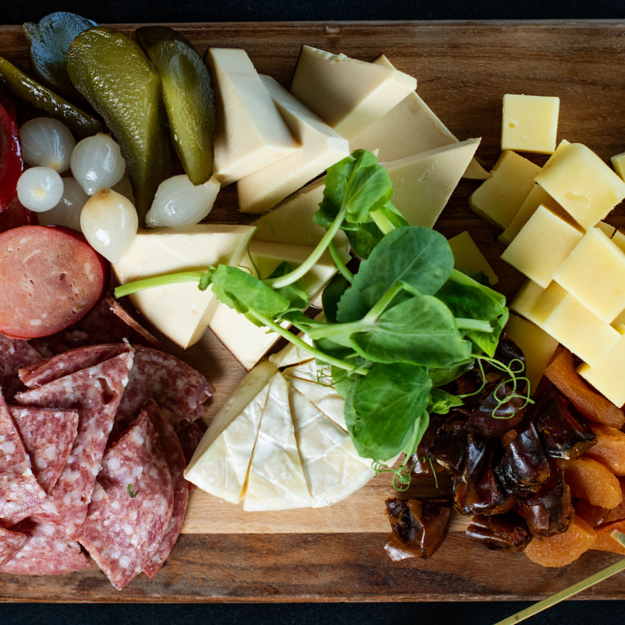 A board with cheese, salami and other food items